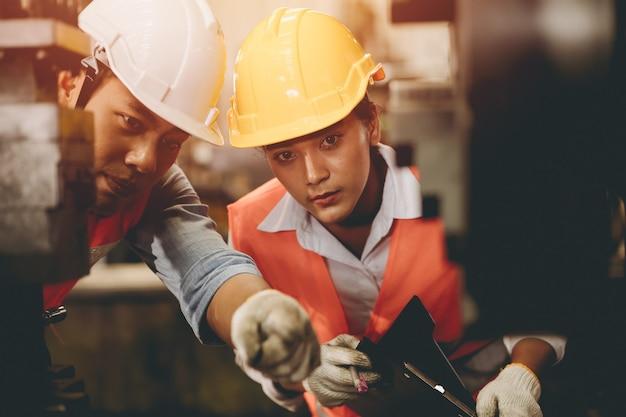 Zespół inżynierów pracujących z kobietami pomaga wspólnie wspierać w przemyśle ciężkim uczyć i szkolić obsługę maszyn w fabryce