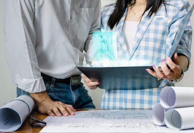 Zespół inżynierów pracuje nad projektem modelu budynku opartego na technologii wyświetlania planu arkusza