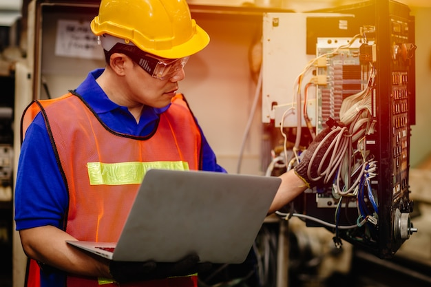 Zespół inżynierów serwisowych pracujący z elektronicznym tylnym panelem maszyny przemysłu ciężkiego w celu naprawy konserwacyjnej i naprawy z komputerem przenośnym w celu analizy problemów.