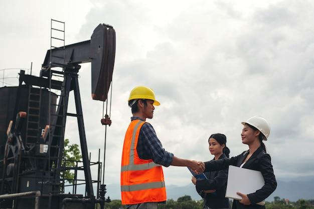 Zespół inżynierów stoi obok pracujących pomp olejowych z niebem.