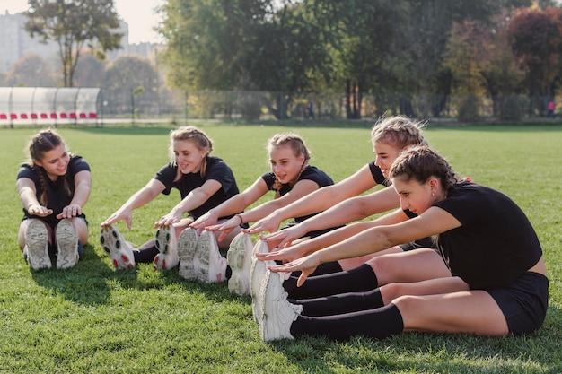 Zespół kobiet robi ćwiczenia rozgrzewkowe