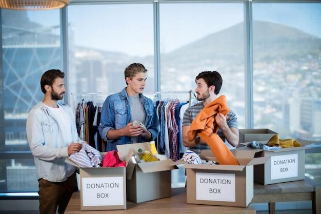 Zespół kreatywnych biznesów sortuje ubrania w skrzynce na datki w biurze