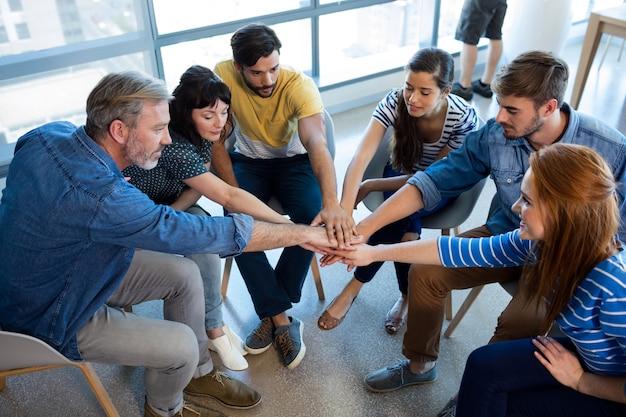Zespół kreatywnych firm, łącząc ręce w biurze