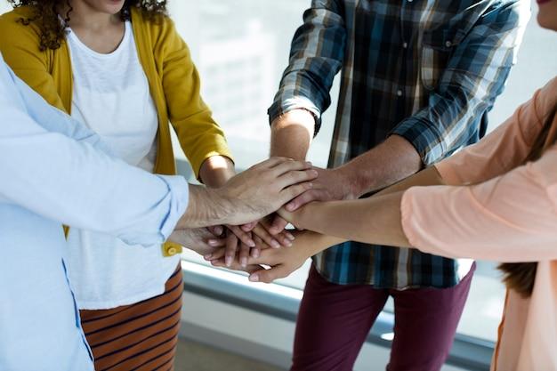 Zespół kreatywnych firm układanie rąk razem w biurze