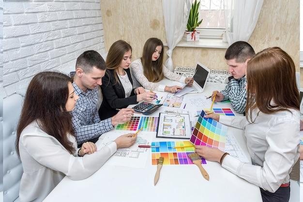 Zespół kreatywnych projektantów omawiający próbkę koloru