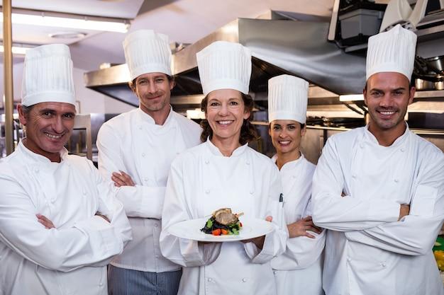 Zespół kucharzy z jednym prezentującym danie