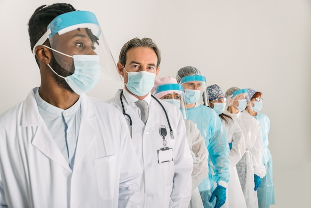 Zespół lekarzy i pielęgniarek w jednorazowych kombinezonach ochronnych i maskach na twarz do walki z covid19
