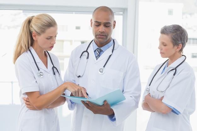 Zespół lekarzy pracujących razem na akta pacjentów