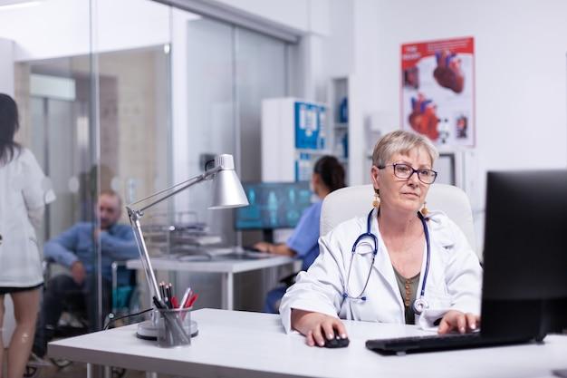 Zespół lekarzy pracujących w szpitalnej klinice, piszący na komputerze, pielęgniarka analizująca skan ciała, podczas gdy młody medyk dyskutuje z niepełnosprawnym szaleńcem w poczekalni. lekarz ekspert pracujący na komputerze, wprowadzający dane