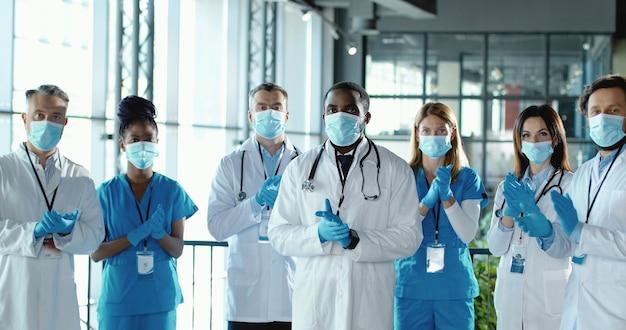 Zespół lekarzy rasy mieszanej, bijący brawa w szpitalu. międzynarodowa grupa medyków w maskach medycznych. chronieni pracownicy. wielu etnicznych lekarzy i pielęgniarki w mundurach w klinice aplauz