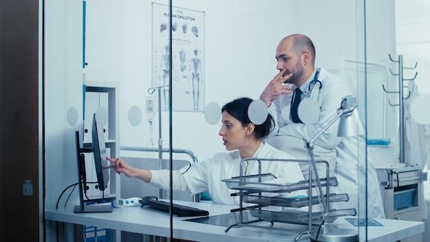 Zespół lekarzy rozmawiających przez szklaną ścianę, wskazujących na ekran komputera, podczas gdy ludzie spacerują korytarzem. system opieki zdrowotnej, prywatna klinika nowoczesnego szpitala medycznego