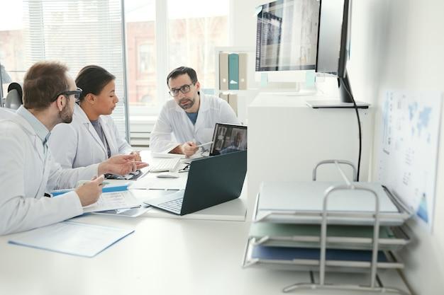 Zespół lekarzy siedzi przy stole i wspólnie omawia problemy podczas spotkania biznesowego w biurze