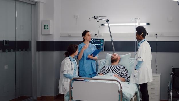 Zespół lekarzy sprawdzający chorego mężczyznę omawiający objawy choroby