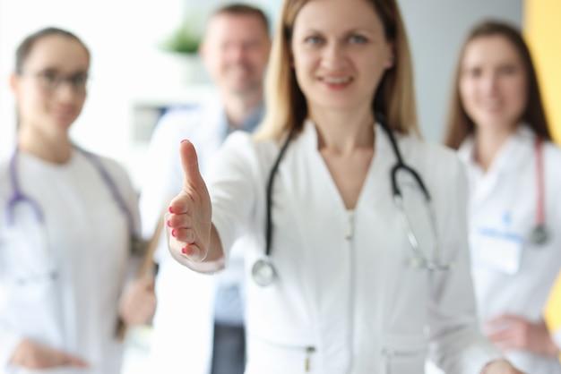 Zespół lekarzy w białych fartuchach uśmiecha się i wyciąga ręce w przyjaznym geście