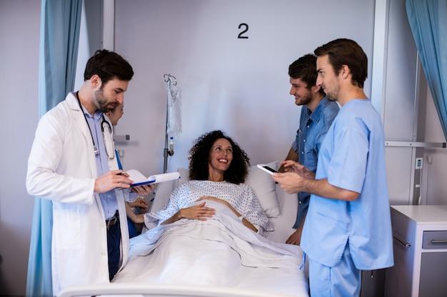 Zespół lekarzy wchodzących w interakcje z kobietą w ciąży