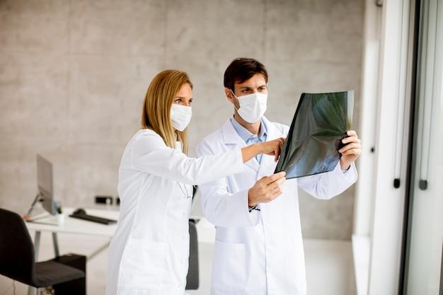 Zespół lekarzy z ochronnymi maseczkami na twarz badający promieniowanie rentgenowskie w gabinecie