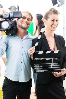 Zespół lub kamerzysta z kamerą i kobieta z klaskaniem lub deską na planie filmowym