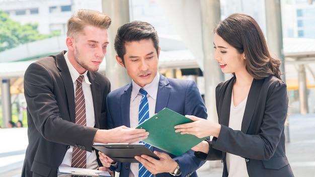 Zespół ludzi biznesu inteligentny mężczyzna i kobieta rozmawiać w godzinach szczytu z aktami obecnych papierkowej roboty na zewnątrz pieszego.