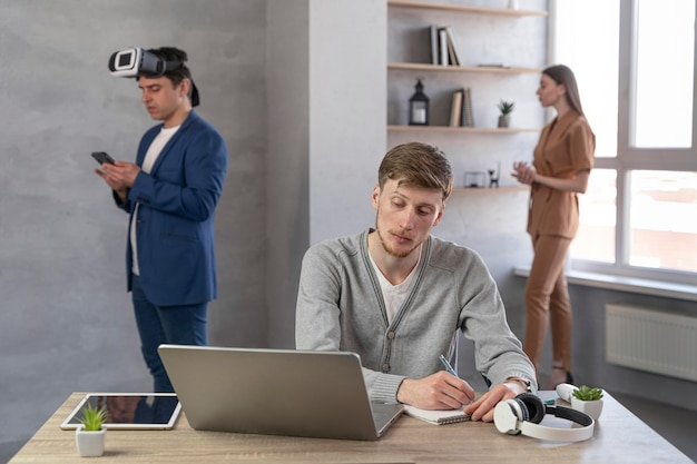 Zespół ludzi korzystających z laptopa i zestawu słuchawkowego do wirtualnej rzeczywistości