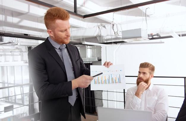 Zespół ludzi pracuje razem nad statystykami firmy w biurze. koncepcja pracy zespołowej i partnerstwa