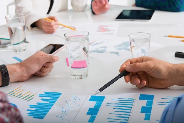 Zespół ludzi pracuje razem nad statystykami firmy w biurze. pojęcie pracy zespołowej i partnerstwa