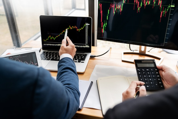 Zespół maklerów giełdowych dyskusje z ekranami wyświetlacza analizowanie danych