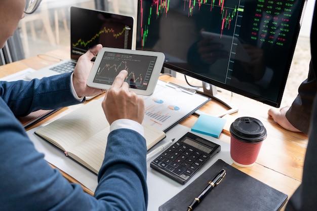 Zespół maklerów giełdowych dyskusje z ekranami wyświetlacza analizowanie danych.