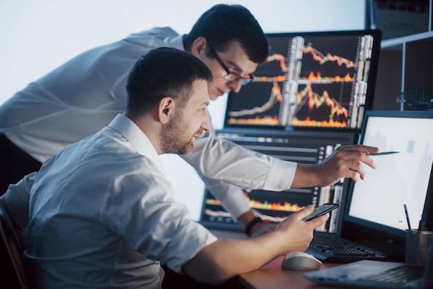 Zespół maklerów prowadzi rozmowę w ciemnym biurze z ekranami. analiza danych, wykresów i raportów do celów inwestycyjnych. kreatywni handlowcy pracy zespołowej
