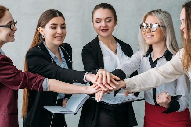 Zespół marketingu korporacyjnego. jedność i współpraca. uśmiechnięte kobiety biznesu kłaść ręce razem.