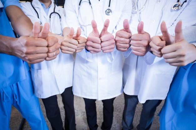 Zespół medyczny kładący kciuki do góry w szpitalu