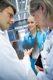Zespół medyczny omawiający raport rentgenowski na korytarzu