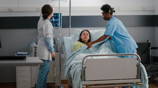 Zespół medyczny pomagający chorej kobiecie kłaść się do łóżka podczas nagłej choroby