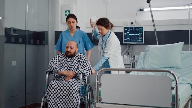 Zespół medyczny pomagający choremu pacjentowi ze złamaniem nogi w wózku inwalidzkim