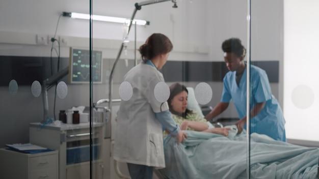 Zespół medyczny pomagający pacjentowi kłaść się do łóżka podczas nagłego wypadku chorobowego