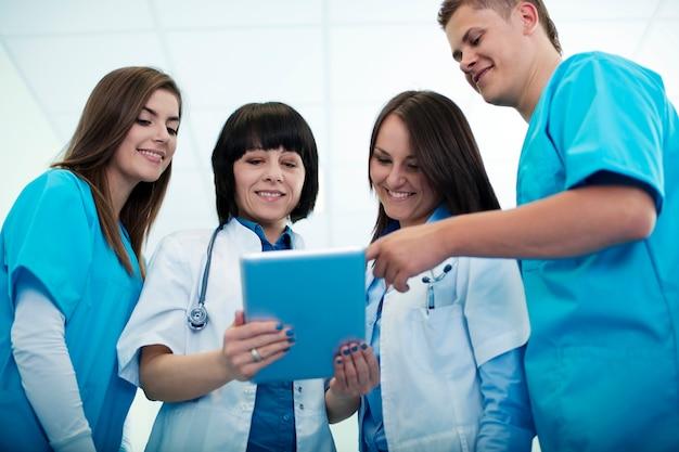 Zespół medyczny sprawdzający wyniki na cyfrowym tablecie