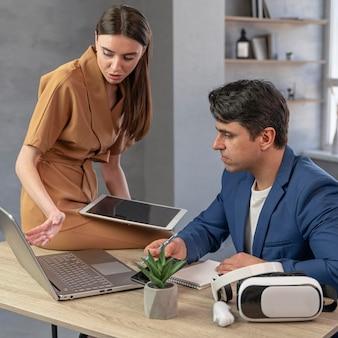 Zespół mężczyzny i kobiety pracującej w dziedzinie mediów z laptopa i tabletu