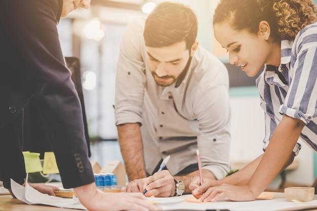 Zespół młodego architekta projektanta burzy mózgów w biurze z papierowym planem na stole, dla zróżnicowanej nowoczesnej koncepcji współpracy biznesowej