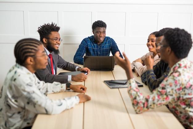 Zespół młodych afrykańskich ludzi pracujących w biurze przy stole z laptopem