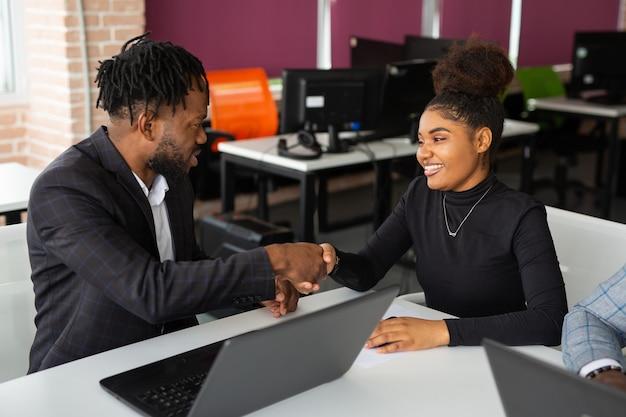 Zespół młodych afrykańskich ludzi w biurze w pracy przy stole z laptopem z uściskiem dłoni