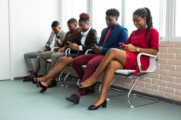 Zespół młodych afrykańskich ludzi w biurze z telefonami komórkowymi