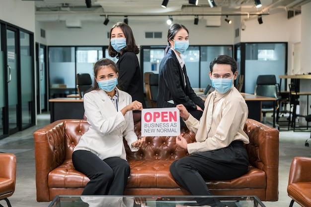 Zespół młodych azjatyckich biznesów noszących maskę z tabliczką otwiera biznes jako nowy normalny na skórzanej kanapie