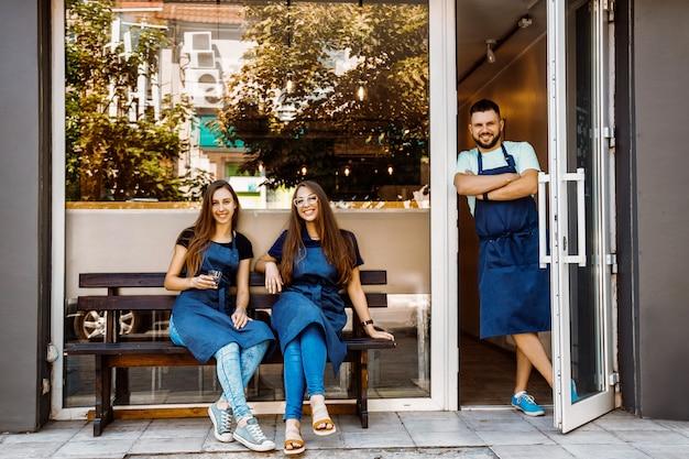 Zespół młodych baristów w pobliżu kawiarni