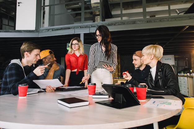 Zespół młodych biznesmenów wykorzystujących technologię na nieformalnym spotkaniu poświęconym projektowaniu architektów. studenci zagraniczni wspólnie uczą się w bibliotece uniwersyteckiej. koncepcja udanego uruchomienia