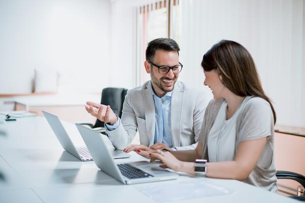 Zespół młodych biznesowych pracujących razem na komputerze przenośnym uśmiecha się