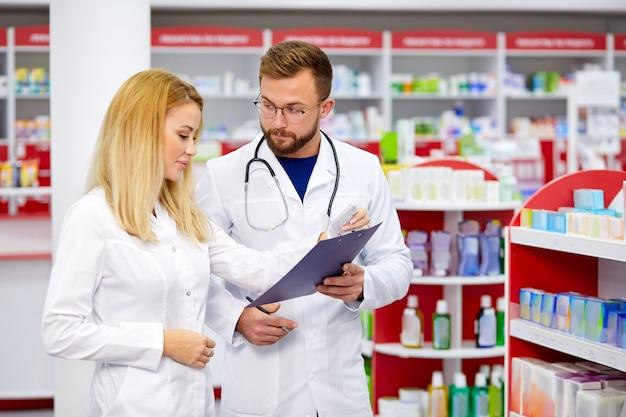 Zespół młodych chemików lub aptekarzy rasy kaukaskiej rozmawiający o lekach