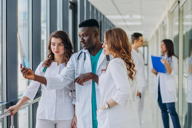 Zespół młodych lekarzy specjalistów stojących na korytarzu szpitala