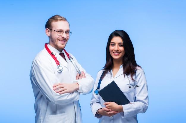 Zespół młodych lekarzy. wielonarodowi ludzie - lekarz, pielęgniarka i chirurg w niebieskim tle. do celi zagląda grupa studentów medycyny różnych narodowości.