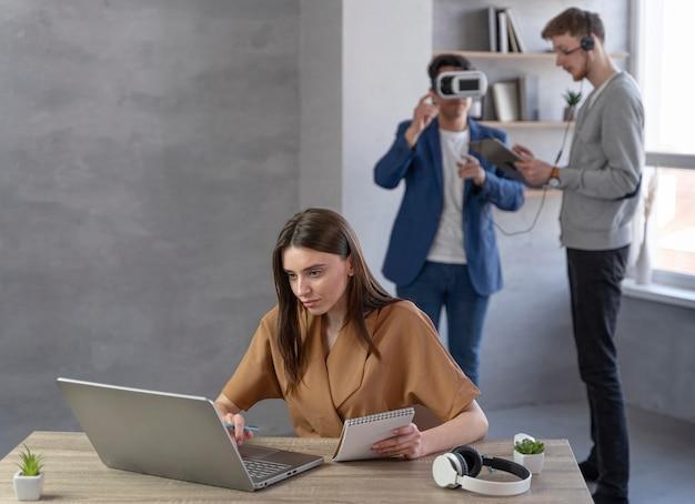 Zespół młodych ludzi korzystających z laptopa i zestawu słuchawkowego wirtualnej rzeczywistości