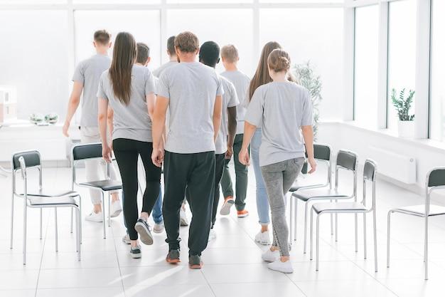 Zespół młodych ludzi przechodzi przez lekkie biuro