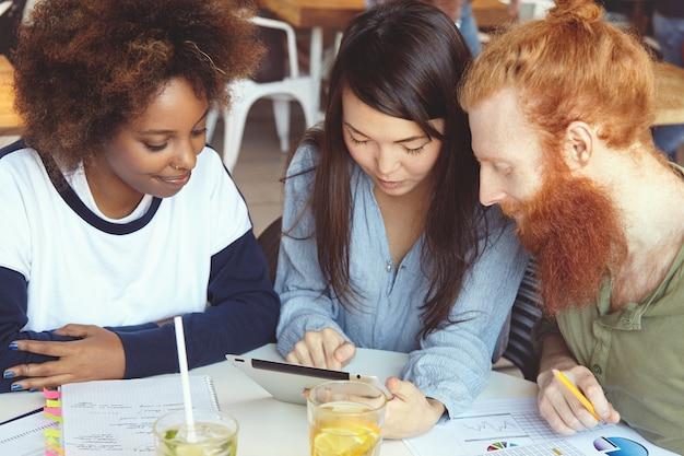 Zespół młodych ludzi z różnych grup etnicznych burzy mózgów, omawiając biznesplany i pomysły na wspólny projekt, wyglądający entuzjastycznie.